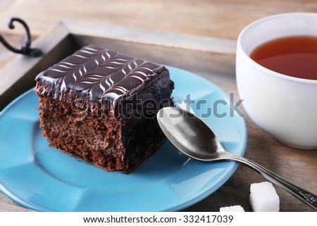 Sweet chocolate cake on blue plate with cup of tea on wooden tray - stock photo
