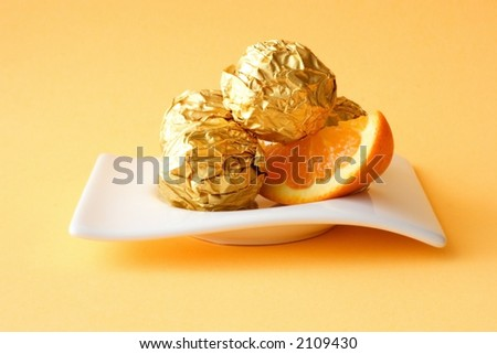 Sweet chocolate cakes with orange stuff on orange background, close-up - stock photo