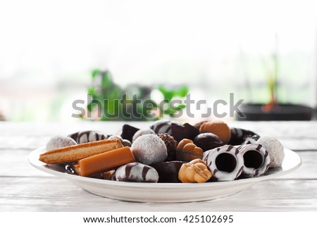 Sweet chocolate candies on white plate on white table in the room. Focus on foreground. Sweet plate from side view. Plate with chocolate candies and cookies. - stock photo