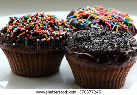 Sweet chocolate cupcake. Close up of chocolate cupcake. Muffins. Fresh delicious homemade cupcakes. Chocolate cupcakes with chocolate frosting on top with sugar sprinkles. Shallow depth of field.  - stock photo