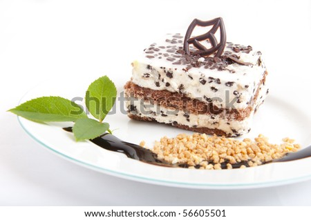 Sweet chocolate dessert with nuts and chocolate on white plate - stock photo