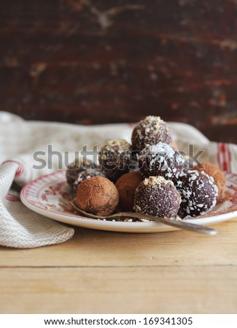 Sweet chocolate truffles with cocoa powder, chopped nuts and coconut on a dessert plate perfect for celebrations as Valentine Day, Easter, Mother Day, Birthday