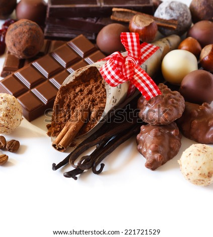 Sweet chocolates and spices on a white background. - stock photo