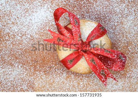 Sweet Christmas mince pie with a red ribbon tied round it on a wooden cooling board with icing sugar. - stock photo