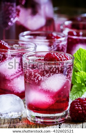 Sweet cocktail with raspberries, ice and soda, vintage wooden background, selective focus - stock photo