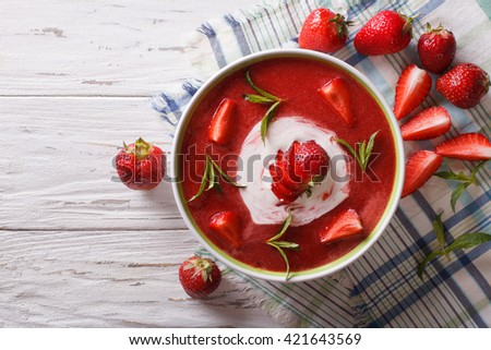 Sweet cold strawberry soup with mint and sour cream in a bowl close-up. Horizontal view from above