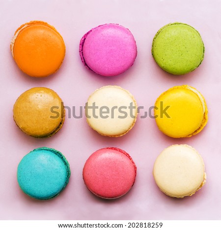 Sweet colorful macaroons on pink background - stock photo