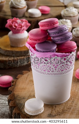 Sweet composition made of popular French bakery called macarons and interestingly designed cupcakes with creamy flowers. Wooden pieces.