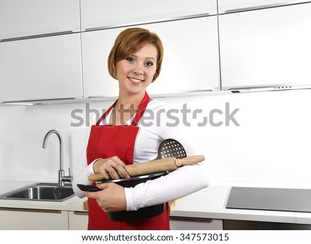 sweet cook woman wearing red apron holding cooking pot and rolling pin at home kitchen smiling happy in domestic cooking and lifestyle concept