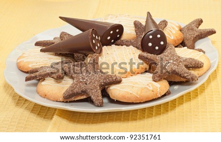Sweet cookies and chocolate on white plate, yellow background