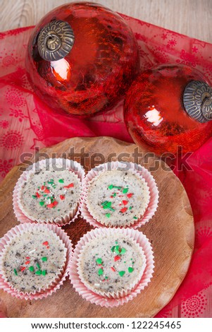 Sweet cookies and cream cheesecakes in muffin forms with red Christmas tree balls - stock photo