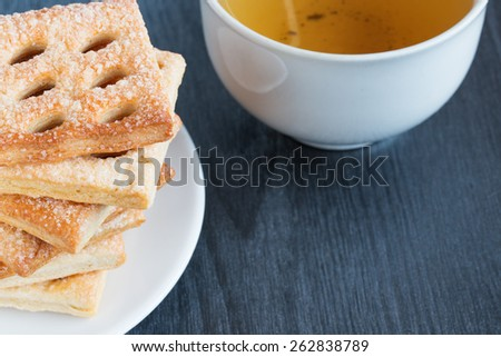 Sweet cookies and cup of tea on a gray wooden table - stock photo