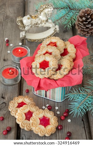 Sweet cookies with jam, fir branches and cones, cranberries, two red burning candles and toy rocking horse on the old wooden table