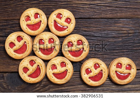 Sweet cookies with jam on wooden background, top view - stock photo
