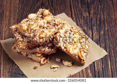 Sweet cookies with nuts, sesame and sunflower seeds on old wooden table - stock photo