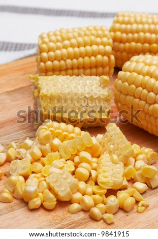 Sweet corn kernels being cut off from the cob on a wooden chopping board - stock photo