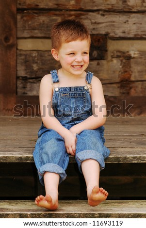 Sweet country boy gets a laugh on the porch of a log cabin - stock photo