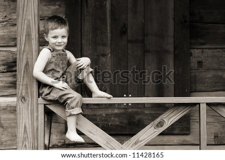 Sweet Country boy sits on a porch railing- with copy space - stock photo