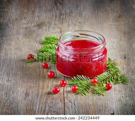 Sweet cranberry jam in jar on wooden background