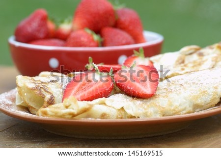 Sweet crepes with strawberries on garden table.