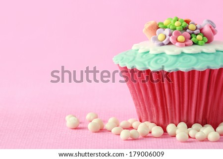 Sweet Cupcake with flower decoration in pink - stock photo