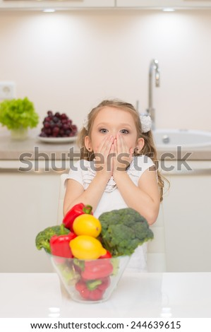 Sweet cute young girl with two ponytails is surprised.  Bowl full of healthy ripe colorful vegetables and fruits.  - stock photo