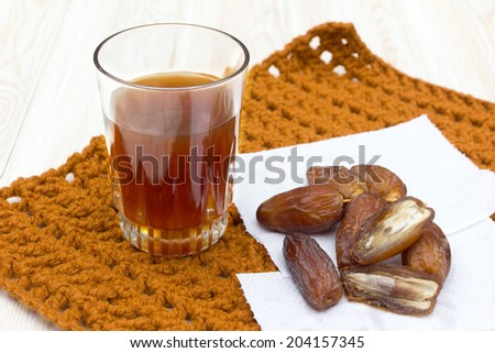 Sweet dates and tea on wood  - stock photo