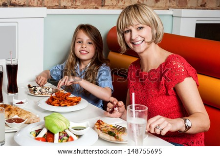 Sweet daughter with her mother in a restaurant - stock photo