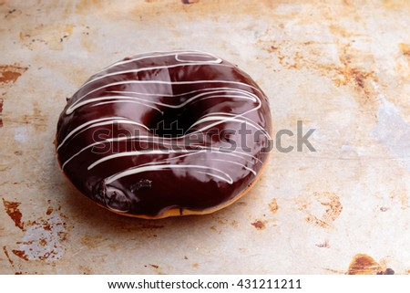 sweet delicious chocolate donut on steel plate - stock photo