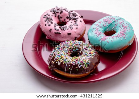 sweet delicious color donuts on red plate - stock photo