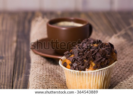 Sweet delicious cupcake decorated by chocolate chips near brown beautiful cup of aromatic coffee standing on sackcloth tasty lunch fattening meal studio closeup on wooden background, horizontal  - stock photo