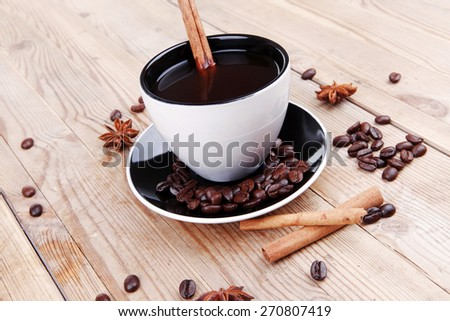 sweet dessert : black coffee and chocolate cake with cinnamon , coffee beans, and anise star on wooden table - stock photo