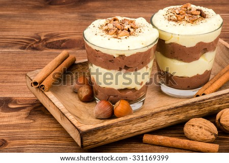 Sweet dessert - chocolate and vanilla pudding in glasses served on the wooden tray with nuts and  cinnamon sticks. - stock photo