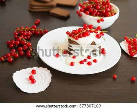 Sweet dessert. Chocolate cookies with a sweet vanilla sauce and fresh red currants berries  - stock photo
