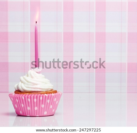 Sweet dessert, cupcake  with butter cream over pink background. - stock photo