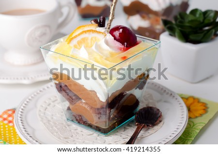 Sweet dessert in glass with biscuit,berry fruit and whipped cream