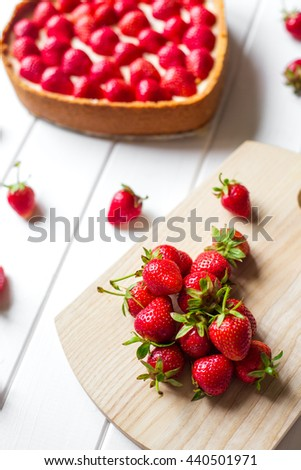 Sweet dessert on a white wooden background. Heart of strawberries - stock photo