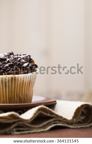 Sweet dessert traditional cupcake in paper form with many calories and carbohydrates unhealthy food decorated by chocolate crumb lunch foodstuff studio copyspace on light background closeup, vertical  - stock photo