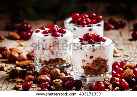Sweet dessert with cranberries, yogurt, cereal, oatmeal and nuts, served in glasses, vintage wooden background, selective focus - stock photo