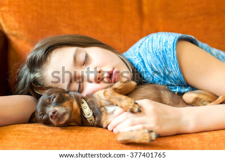 Sweet dream. Young girl sleeping hugging her lovely little brown Toy-terrier dog on a coach. Multicolored vibrant horizontal indoors image - stock photo
