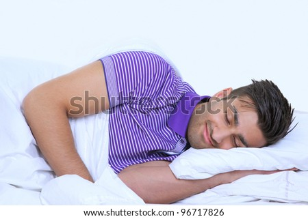Sweet dreams young man asleep in bed - stock photo