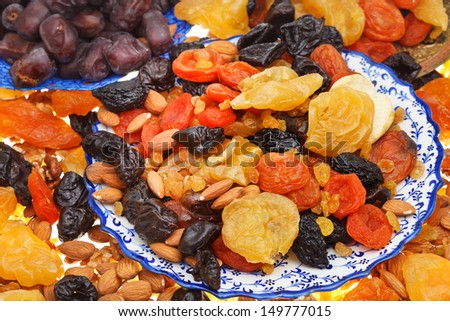 sweet dried fruits on asian plates close up