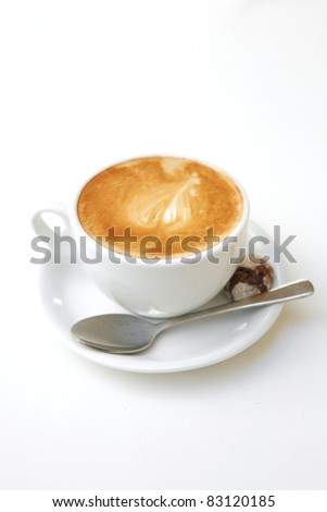 sweet drink : small white cup of cappuccino coffee on light background with spoon - stock photo