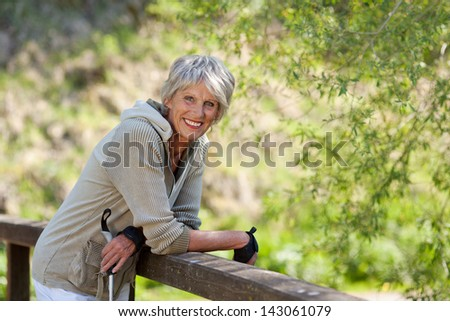 Sweet elderly woman standing inside the park and smiling for the camera. - stock photo