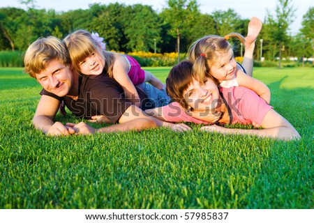 Sweet family playing  on the green grass - stock photo