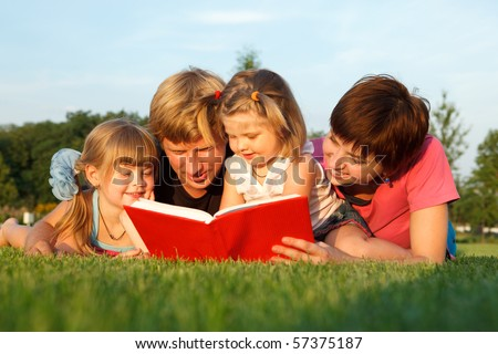 Sweet family reading a book on the green grass - stock photo