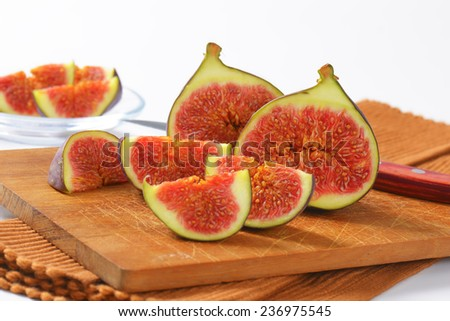 sweet figs halved with sharp knife, served on the wooden cutting board - stock photo