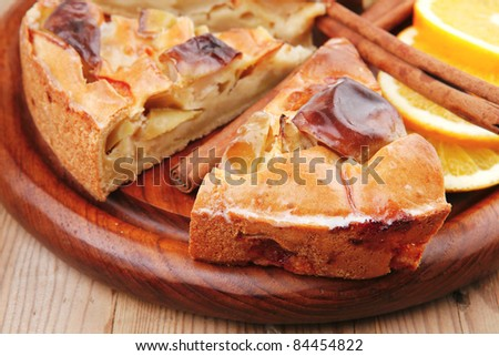 sweet food : apple pie cuts served on wooden plate over table with cinnamon and lemon - stock photo