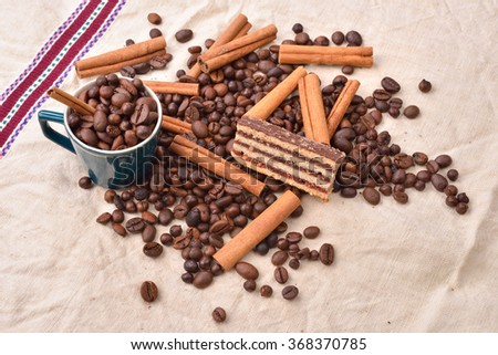 Sweet food. Black beans coffee and chocolate cake with cinnamon stick on jute background.  Morning pleasures. Selective focus - stock photo