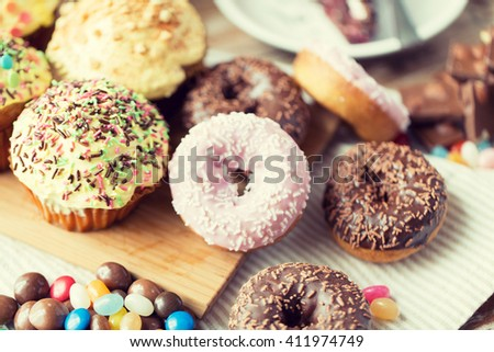 sweet food, junk-food and eating concept - close up of glazed donuts, candies and muffins on wooden board - stock photo